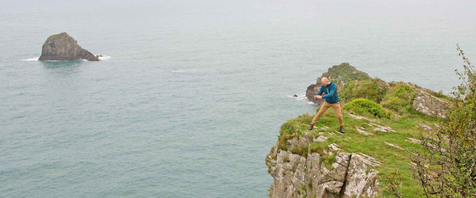 Guest looking over the cliffs into the sea below at Berry Head near Brixham