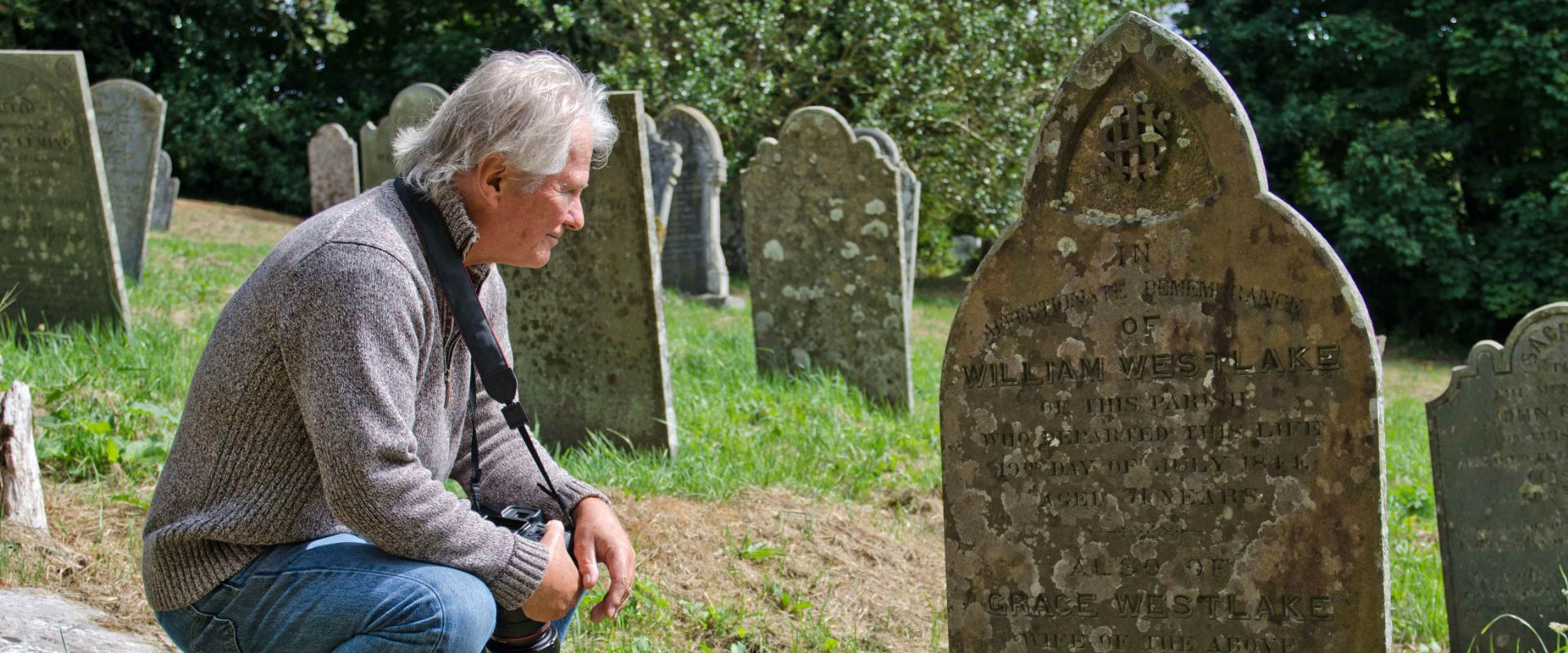 A guest looking at the headstone of his ancestor